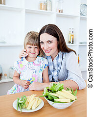 Cute little girl eating vegetables with her mother