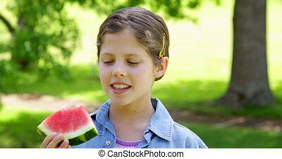 Cute little girl eating watermelon