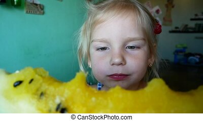 cute little girl eating yellow watermelon