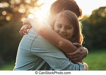 Cute little girl embracing her father on a sunny day