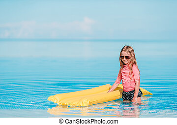 Cute little girl enjoy vacation in the swimming pool