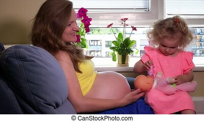 cute little girl feed toy baby with bottle sitting on her pregnant mother knees