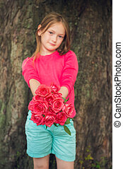 Cute little girl giving beautiful bouquet of bright pink roses