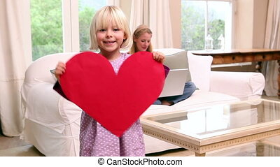 Cute little girl giving her mother a heart card at home in...