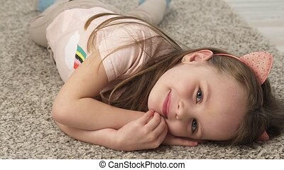 Cute little girl grimacing and smiling while lying on the...