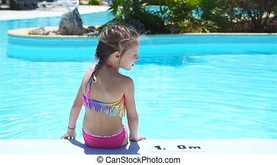 Cute little girl having fun in outdoor swimming pool