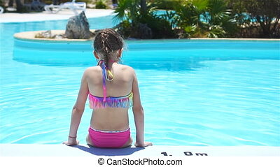 Cute little girl having fun in outdoor swimming pool. SLOW MOTION