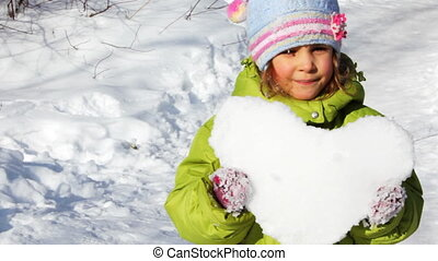 little girl hold heart made of snow and stand on trail -...