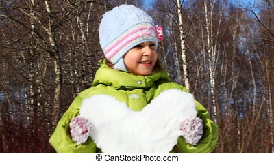 cute little girl hold heart made of snow, smile and spin