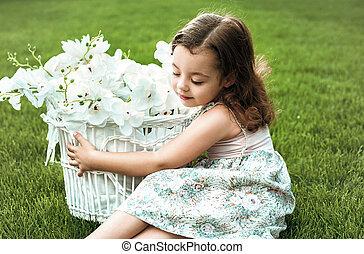 Cute little girl holding a basket full of flowers