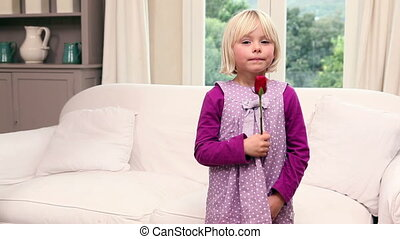 Cute little girl holding a red rose
