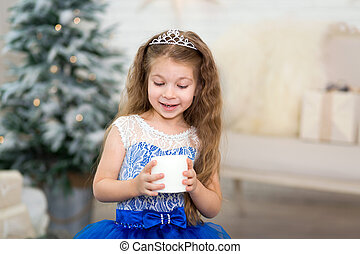 Cute little girl holding an artificial candle in her hands for home decoration for the Christmas holidays. Child-friendly scenery