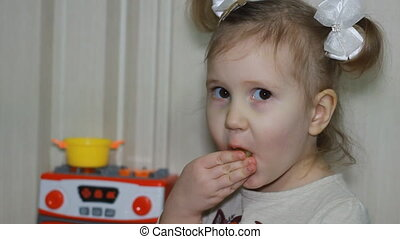 Cute little girl holding an orange eats and and waves his hand good-bye. Close-up portrait.