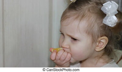 Cute little girl holding an orange eats and curves the face....