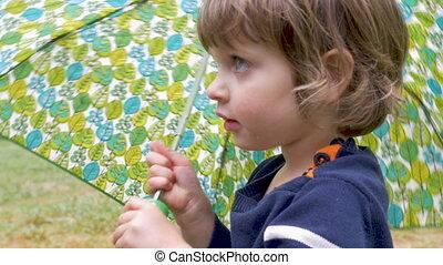 Cute little girl holding an umbrella turns and walks away -...