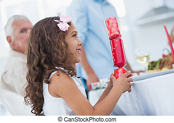 Cute little girl holding crackers at table for christmas ...