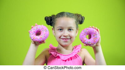 Cute little girl holding donuts with icing in her hands, smiling, looking at the camera and bringing them to her face, makes glasses from sweet donuts with pink icing. Portrait of a child