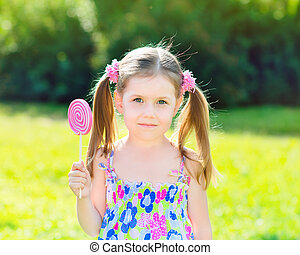 Cute little girl holding lollipop