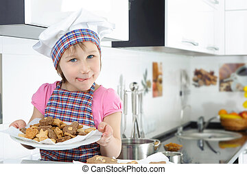 Cute little girl holding plate with cookies
