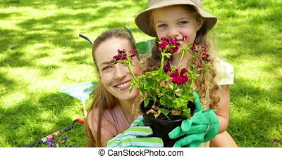 Cute little girl holding pot of flowers with her mother on a...