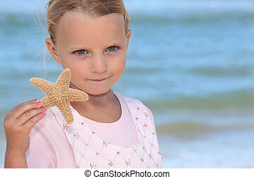 cute little girl holding starfish against sea background