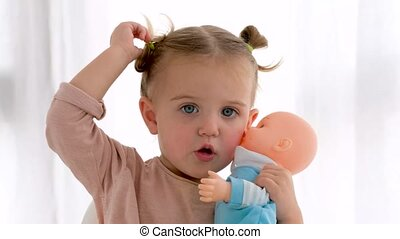 Adorable little girl with pigtails looking at camera and hugging baby doll white background