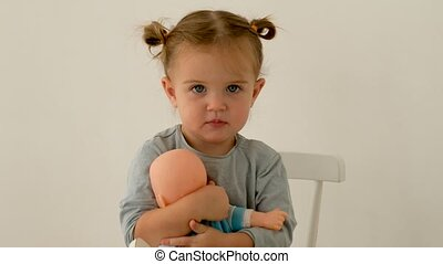 Adorable little girl with pigtails looking at camera and hugging baby doll while sitting on chair on gray background