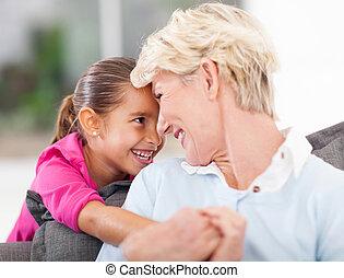 cute little girl hugging grandma at home
