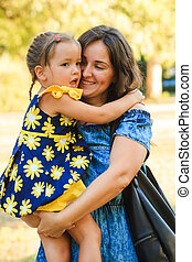 cute little girl hugging her mother outdoor shot in park