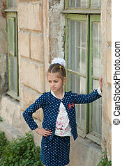 cute little girl in a fashionable costume is standing by the house