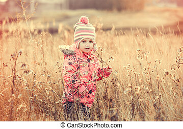 cute little girl in a field at sunset