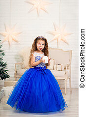 Cute little girl in a magnificent blue dress holding an artificial candle in her hands for home decoration on Christmas holidays. Child-friendly scenery