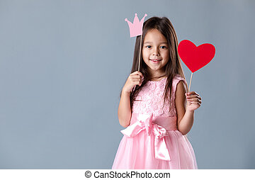 cute little girl in a pink dress holding a paper heart