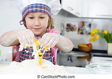 Cute little girl in apron cooking cookies