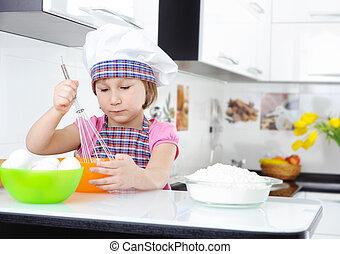 Cute little girl in apron whisking eggs