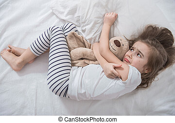 Cute little girl in bed with soft toy.