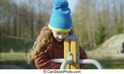 Cute little girl in blue hat playing on the playground. Female turning on the carousel and smiling. Carefree childhood.