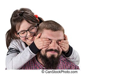 Cute little girl in casual clothes covering her father eyes. Both smiling. Isolated on white. With copy space