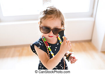 Cute little girl in dress and big sunglasses at home. - Cute...