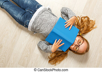Cute little girl in glasses with a book lying on the floor