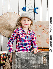 cute little girl in hat sitting in chest