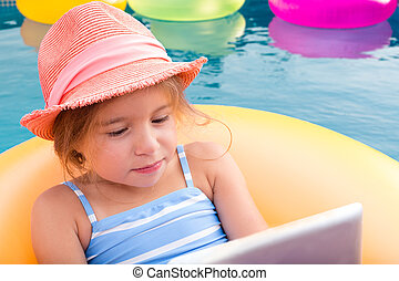 Cute little girl in hat using laptop while in pool