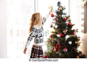Cute little girl in knitted sweater placing star on the top of Christmas tree