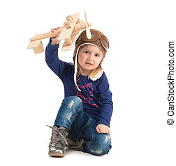 cute little girl in pilot hat with wooden plane
