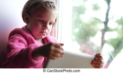Cute little girl in pink bathrobe using tablet pc while Sitting on the window sill.