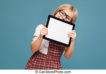 Cute little girl in red dress, white shirt and glasses holds empty tablet