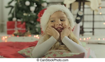 Cute little girl in Santa's hat lying on the pillow near Christmas tree