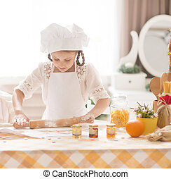 cute little girl in the form of a chef preparing tasty food in kitchen