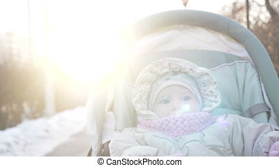 Cute little girl in the pram closeup. Walk with adorable...