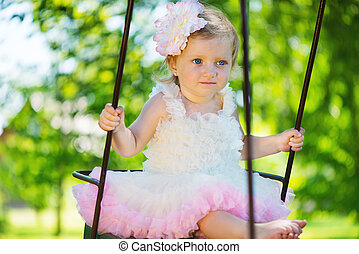 Cute little girl in tutu swinging